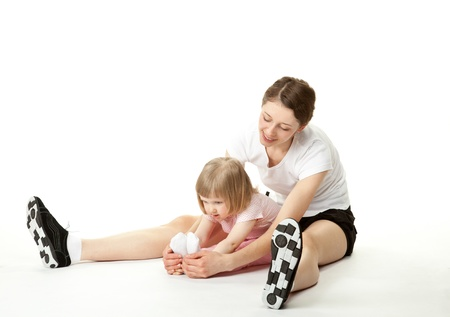 Happy young mother and her little daughter doing sport exercises; white background photo