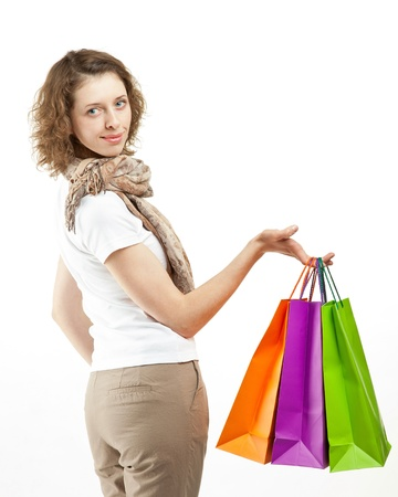 Happy girl holding multicolored shopping bags; white background photo