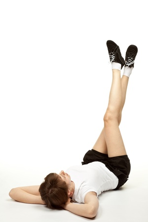 Young woman doing sport exercises lying on the floor; white background photo