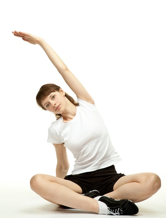 Calm attractive young woman sitting on the floor and doing sport exercises; white background photo