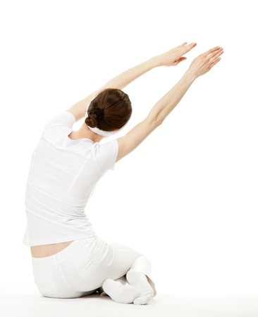 Slender young woman doing sport exercises; rear view on white background photo