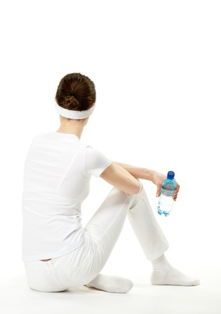 Young woman relaxing after sport; graceful young woman sitting on the floor holding bottle of drinking water, rear view, white background photo