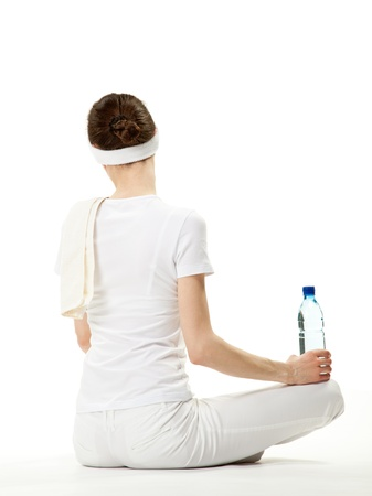 Young woman relaxing after sport; graceful young woman sitting on the floor holding bottle of drinking water, rear view, white background Stock Photo - 13193065