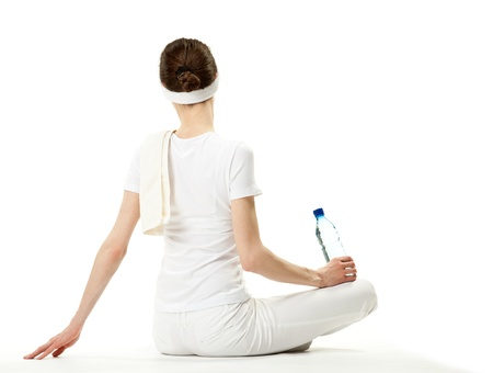 Young woman relaxing after sport; graceful young woman sitting on the floor holding bottle of drinking water, rear view, white background Stock Photo - 13193048