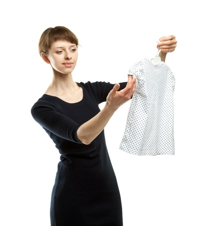 Young mother choosing dress for her little daughter; white background photo
