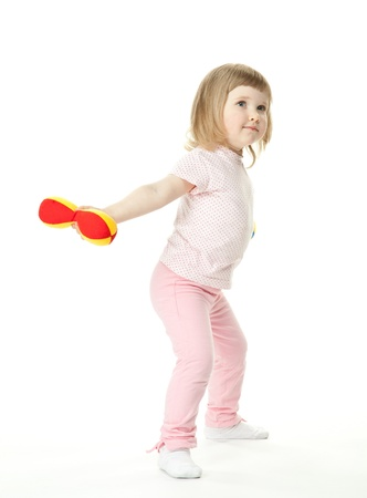 Cute little baby girl doing sport exercises with toy dumbbells; white background Stock Photo