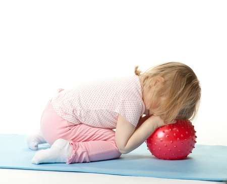 Little child sleeping/relaxing on a ball after sport, white background Stock Photo - 13243557