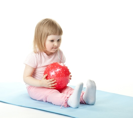Baby girl doing exercises with a ball sitting on a mat; white background photo