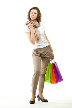 Shopping concept  happy beautiful young woman holding multicolored paper bags; full length portrait on white background photo
