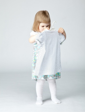 Adorable little girl choosing dress for herself; neutral background photo