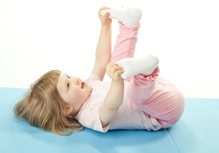 Cute child doing sport exercises on a training mat; white background photo