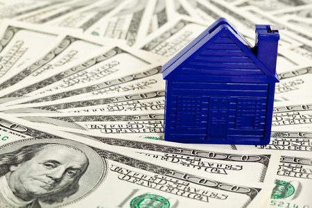 Many dollar banknotes and a house model; concept of buying a house photo
