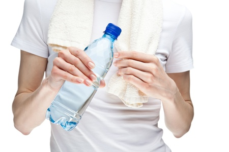 Womans hand holding bottle of drinking water after sport exercises isolated on white photo
