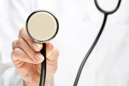 Doctor holding stethoscope; closeup of doctors hand with stethoscope photo