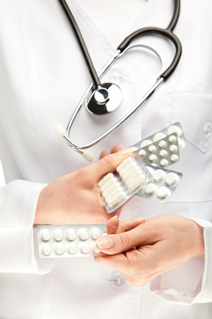 adverse reaction: Doctor prescribing many pills; closeup of doctors hands holding many medicines Stock Photo
