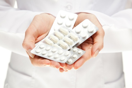 Doctor giving many pills; closeup of doctors hands holding many medicines