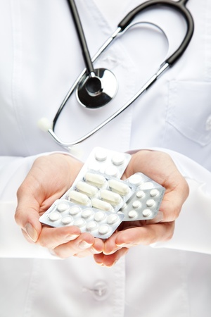 adverse reaction: Doctor prescribing many pills; closeup of doctors hands giving many medicines Stock Photo