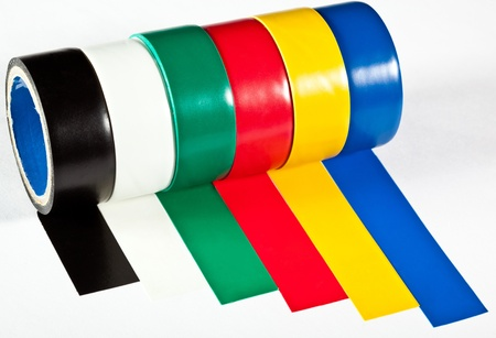 Rolls of insulation adhesive tape; multicolored isolating tape on neutral background
