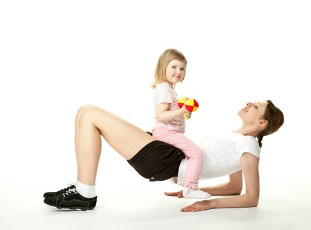 Happy smiling mother doing sport exercises with her little daughter; white background