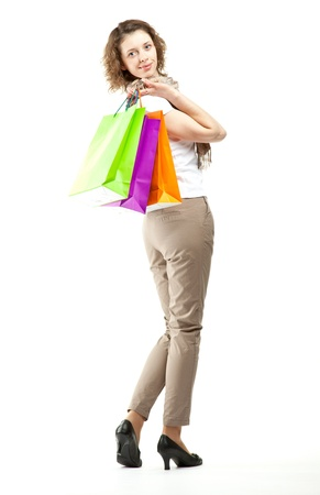 Shopping concept: happy beautiful young woman holding multicolored paper bags; full length portrait on white background photo