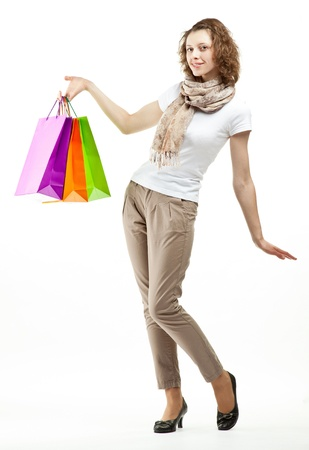 Shopping concept: happy beautiful young woman holding multicolored paper bags; full length portrait on white background Stock Photo - 13533678