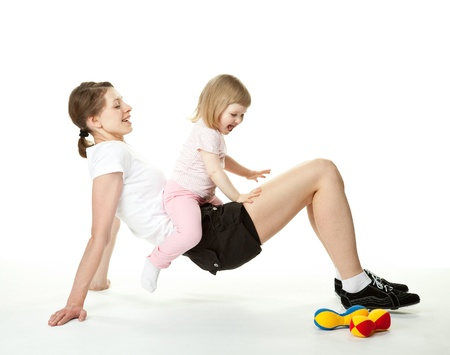 Happy young mother doing sport exercises with her little daughter; white background Stock Photo - 13587056