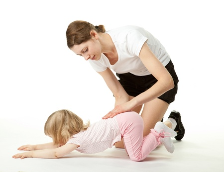 Attractive young mother teaching little daughter to do sport exercises; white background