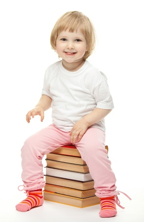 Cheerful baby sitting on stacked books; white background Stock Photo - 13587115