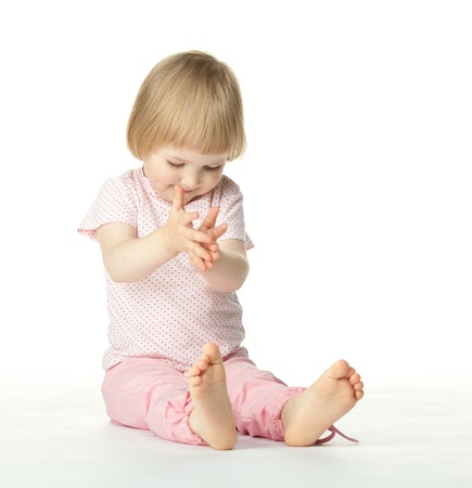 Playful baby girl clapping her hands sitting on the floor; white background photo