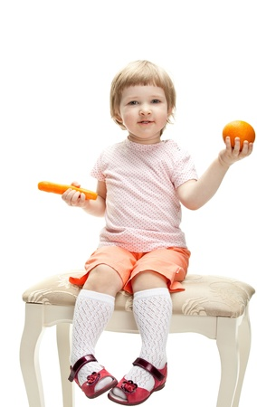 Cute baby girl playing with orange and carrot; white background Stock Photo - 13664941