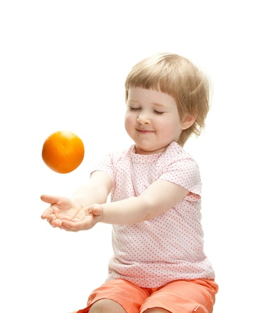 Happy smiling child playing with orange catching it, isolated on white Stock Photo - 13664922