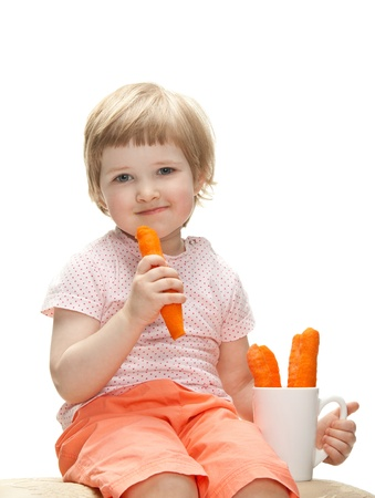 Happy baby eating fresh carrot isolated on white Stock Photo - 13664920