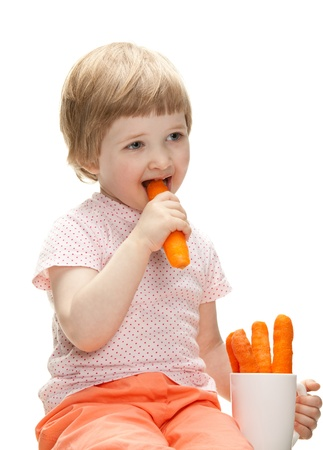 Happy baby eating fresh carrot isolated on white photo