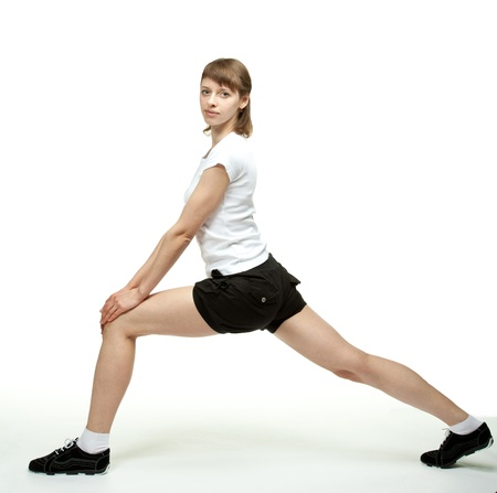 Slender young woman doing sport exercises on white background photo