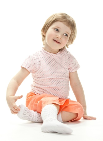 Portrait of a cute little girl sitting on the floor; studio shot on white background Stock Photo - 13664926