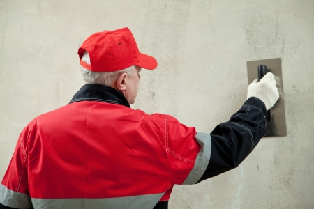 Back view of a plasterer in uniform working with float against the wall photo