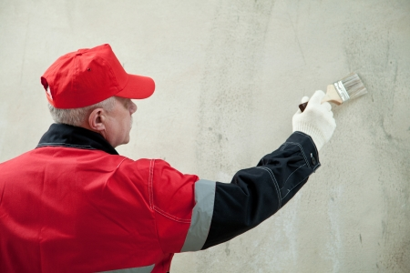 Painter working with paintbrush against the concrete wall photo