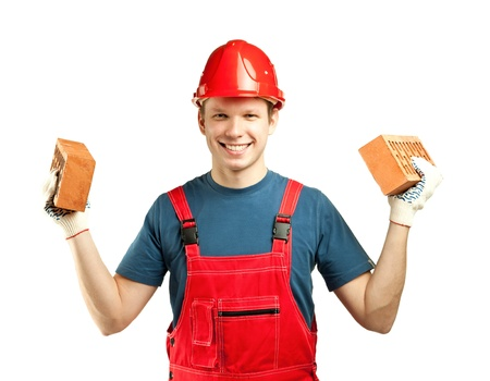 Cheerful builder in uniform and hardhat holding bricks, isolated over white background photo