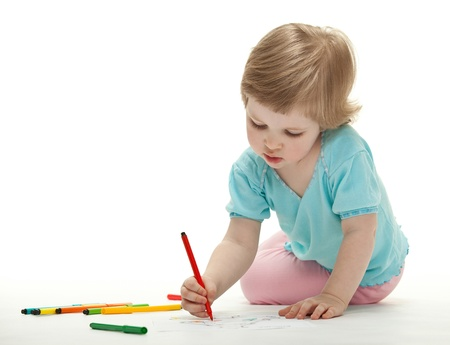 Baby girl drawing with colorful felt-tip pens on white background photo