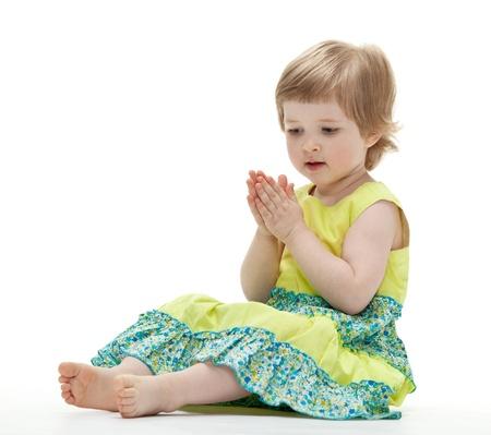 manos aplaudiendo: Bebé que juega sentada en el suelo sobre fondo blanco