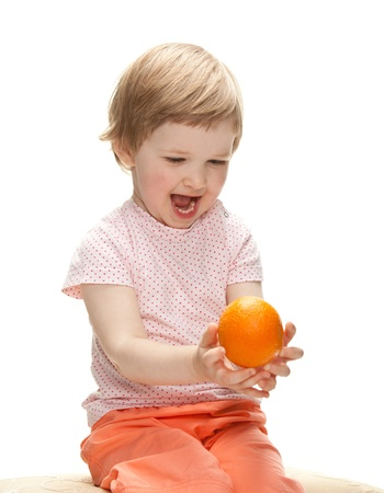 Happy laughing child playing with orange tossing it up, isolated on white Stock Photo - 13847005