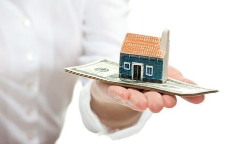 Concept of buying a house: female hand reaching out little house model to you photo