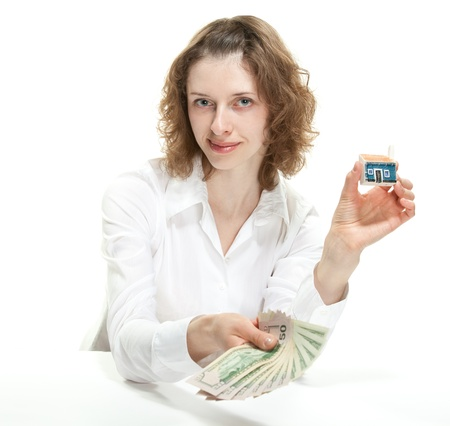 Attractive young woman showing dollar banknotes and small house; concept of investment in real estate photo