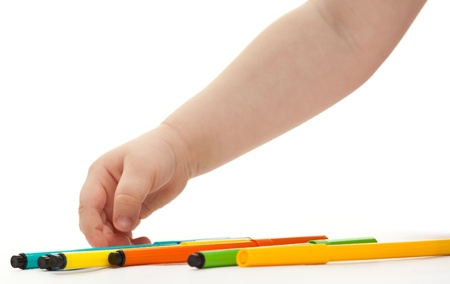Childs hand choosing a felt-tip pen; white background photo
