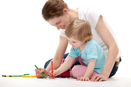 Young mother and her daughter drawing together; white background photo