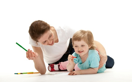 Happy young mother and her daughter drawing; studio shot on white background photo