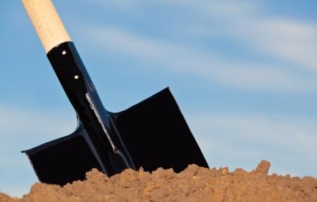 Shovel in the heap of ground against blue sky Foto de archivo