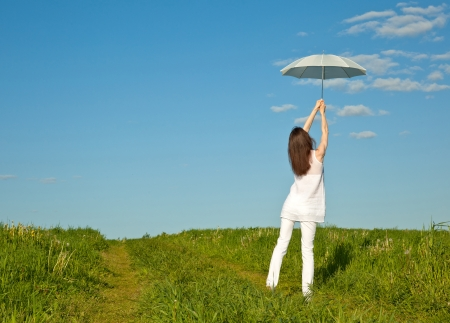 Beautiful girl with white umbrella in summer meadow photo
