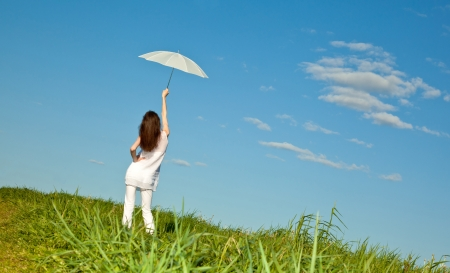 Beautiful brunette girl with white umbrella in a green summer meadow Stock Photo - 13966668