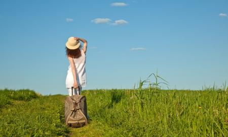 femme valise: Belle jeune femme marche le long du chemin avec une valise, vue arri�re